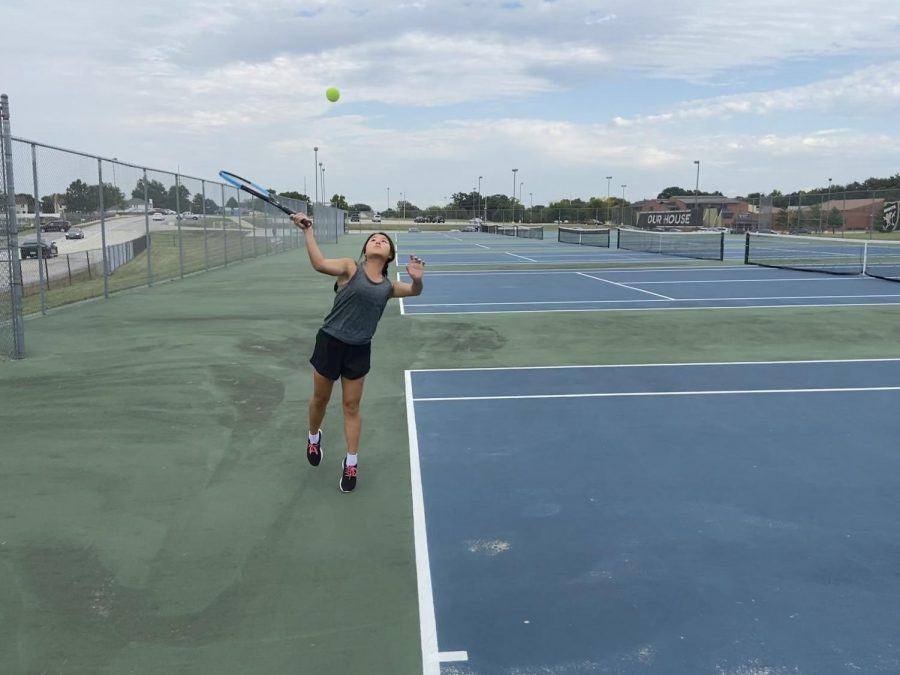Senior Iris Lee serves the tennis ball during practice.