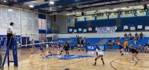 Player number seven, Sara Ausbury, jumps up tall with her teammate, Megan Steutermann as they  raise both arms up, careful not to touch the net, to attempt to block the opponents hit.