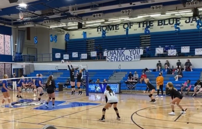 Player+number+seven%2C+Sara+Ausbury%2C+jumps+up+tall+with+her+teammate%2C+Megan+Steutermann+as+they++raise+both+arms+up%2C+careful+not+to+touch+the+net%2C+to+attempt+to+block+the+opponents+hit.+