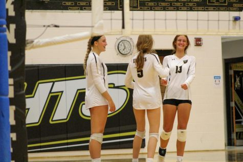 Three varsity volleyball players laugh during a volleyball game. Brianna Wortman did not play in this game but supported her team from the sidelines.