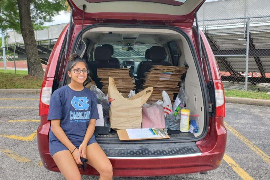 Senior Riya Contractor sits in the back of a car with care packages for charity.