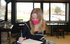 Junior Ellie Miller wears a mask while working in the Learning Commons. Mask-wearing is an important part of ensuring that the new quarantine policy is safe and effective.