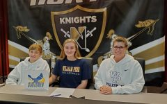 Senior Cate Hahn smiles with her family while signing to William Penn on National College Signing Day on Nov 11