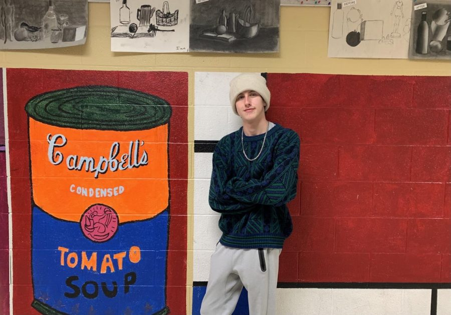Connor Buschmann stands next to murals in the art hallway. He has a passion for art and hopes to grow his skills in street art and spray paint.