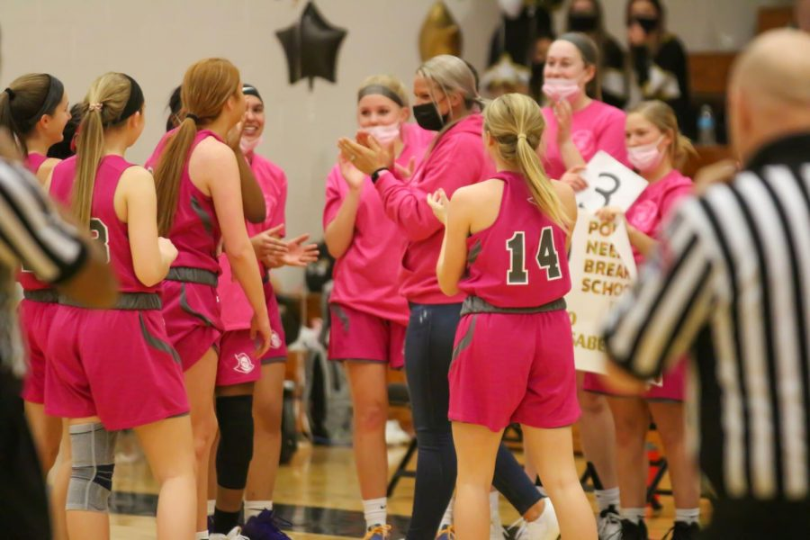 The Lady Knights celebrate with senior Isabelle Delarue at the game. Delarue has set a new record for points scored in FHN girls' basketball.