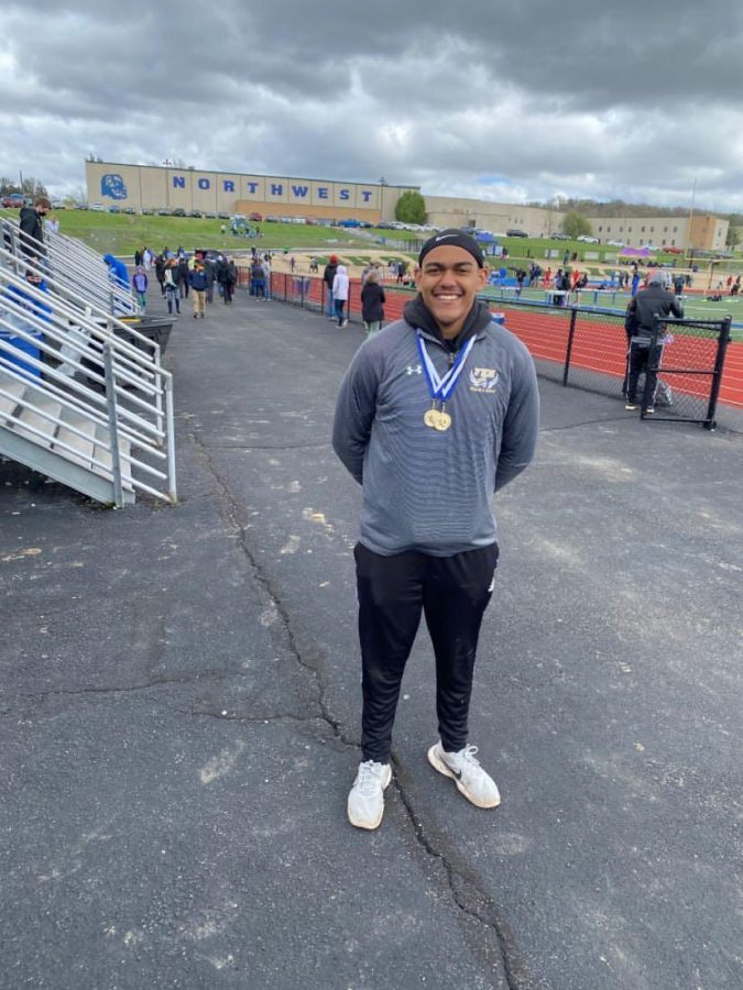 Senior Aaron Okello poses with medals after receiving first place in both boys varsity shotput and discus, at Northwest Invitational.