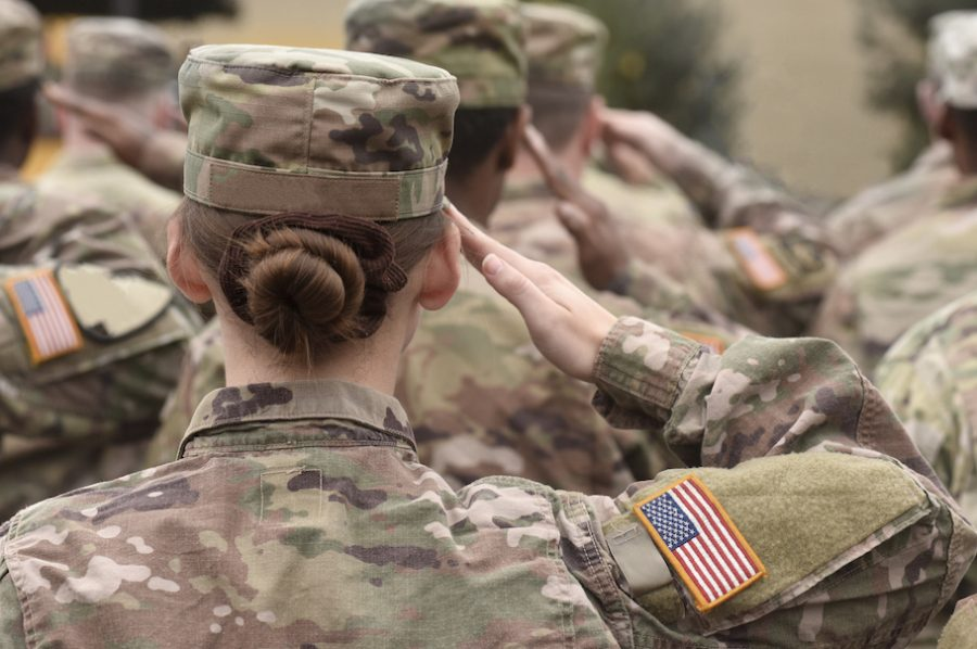 Female American Army soldier salutes in the lineup. (Photo from shutterstock)