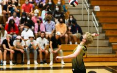 Senior Cole Hopper jumps to hit the volleyball during a game