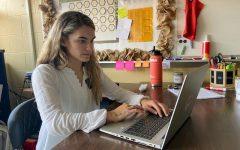 New teacher Rowan Pugh sits at her desk in her classroom