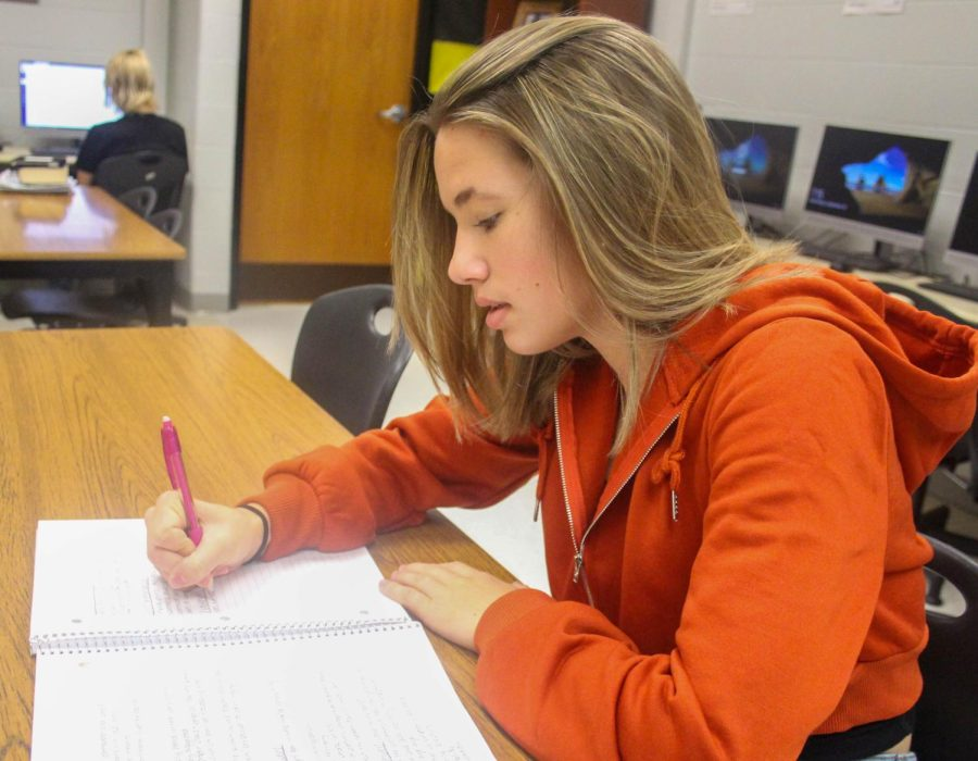 Junior Bailey Scarborough takes down her note on paper in her classroom.