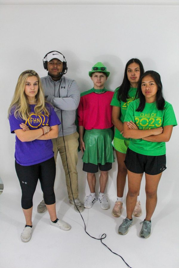Seniors Grace Herbert, Gabe Kasper and juniors Parker Bruns, Amelia Churma, and Joshi Vargas pose in their PowderPuff attire. Hebert is competing, Kasper is a coach for the senior, Bruns is a crowd pleaser and Vargas and Chruma are competing.