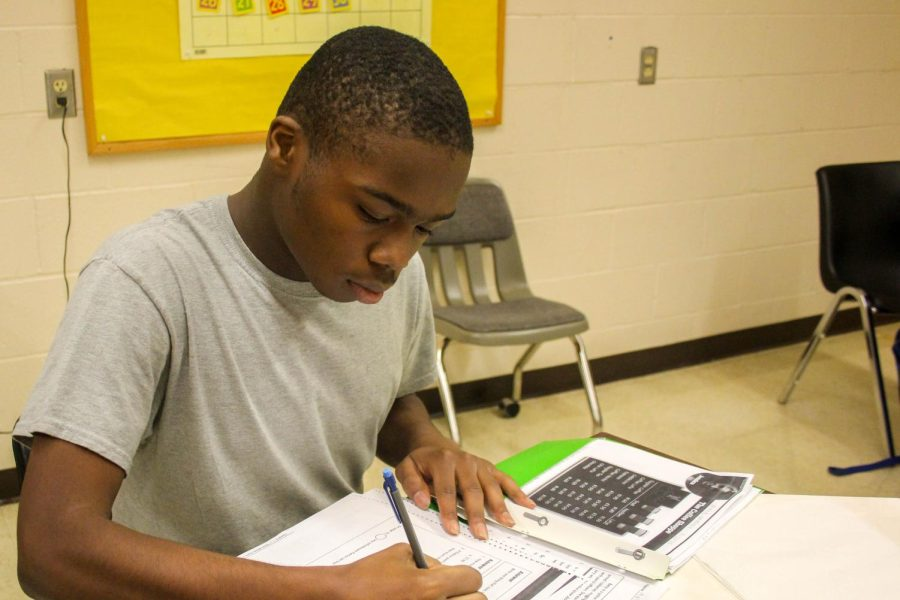 Senior Malik Wallace sits at his desk and does work in the classroom.