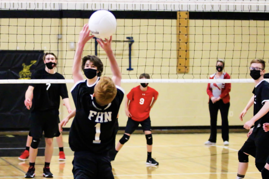 Sophomore Jonathan Davis sets a volleyball during the game.