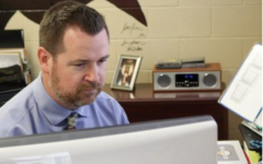 Dr. Lucas Lammer looks up a student in infinite campus in his office.