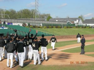 The Varsity Baseball team gathers around home plate to celebrate Senior Mike Wilson's home run.