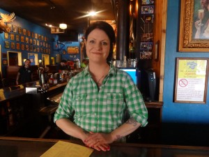 Bar manager Becca Schock stands behind the bar waiting to serve customers.She also greats her guests and bids them good-bye.