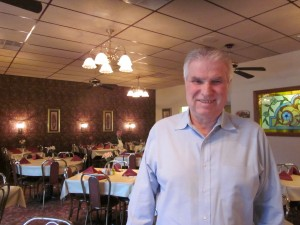 "Pietro ""Pete"" Pulizzi stands in the Erio's, the restaurant he owns with his wife Joan. Joan makes the desserts for the restaurant, such as cheesecake, brownies, and flourless chocolate cake."