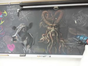 Smithey's chalkboard in room 165 holds more that the daily assignment. Sketches of projects and examples also cover the board. The medium used in these drawings is chalk.