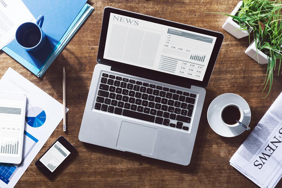 A+laptop+sits+on+a+table%2C+surrounded+by+different+newspapers+and+a+cup+of+tea.+%28Source%3A+Shutterstock%2FStokkete%29